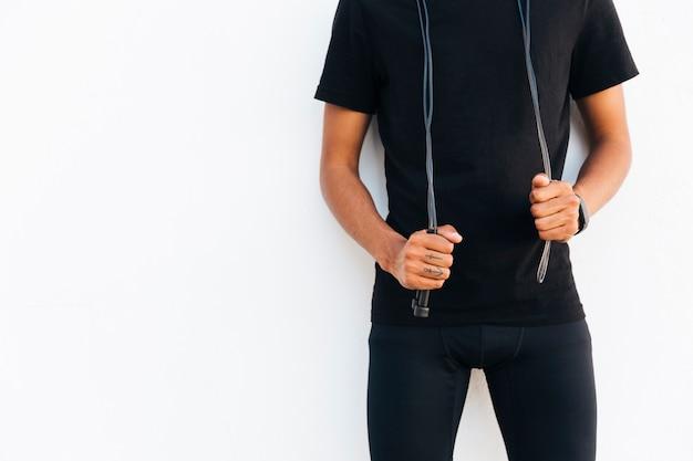Joven negro en negro con cuerda de saltar