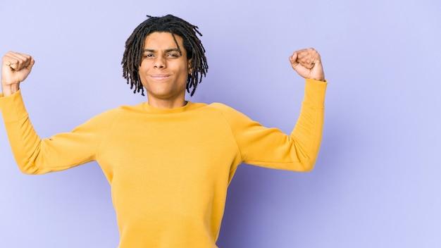 Joven negro con peinado rasta mostrando gesto de fuerza con los brazos, símbolo del poder femenino