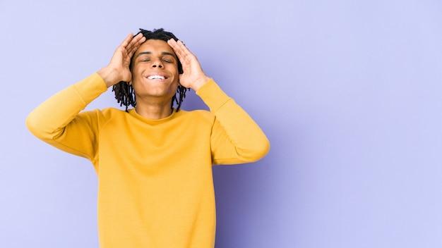 Joven negro con peinado rasta ríe alegremente manteniendo las manos en la cabeza. concepto de felicidad.