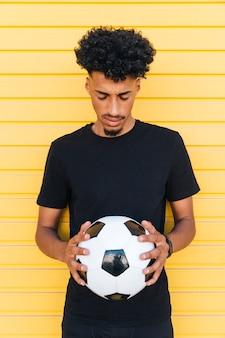 Joven negro con pelota de futbol ojos cerrados