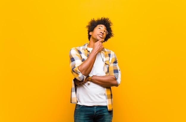 Joven negro pensando, sintiéndose dudoso y confundido, con diferentes opciones, preguntándose qué decisión tomar contra la pared naranja