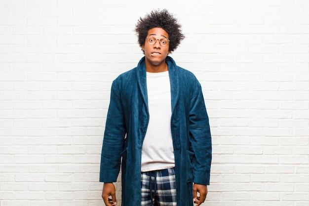 Joven negro con pijama con bata sintiéndose desorientado, confundido e inseguro sobre qué opción elegir, tratando de resolver el problema contra la pared de ladrillo