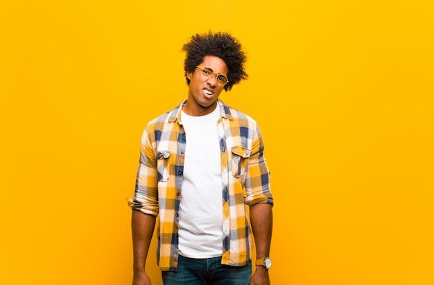 Joven negro que se siente confundido y confundido, con una expresión tonta y atónita mirando algo inesperado contra la pared naranja