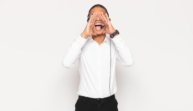Joven negro que se siente feliz, emocionado y positivo, dando un gran grito con las manos al lado de la boca, gritando