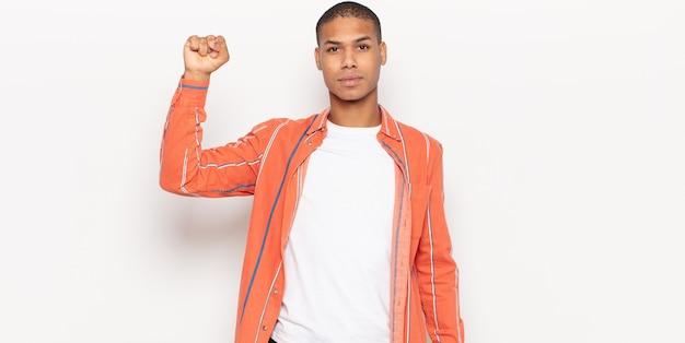 Joven negro que se siente serio, fuerte y rebelde, levanta el puño, protesta o lucha por la revolución