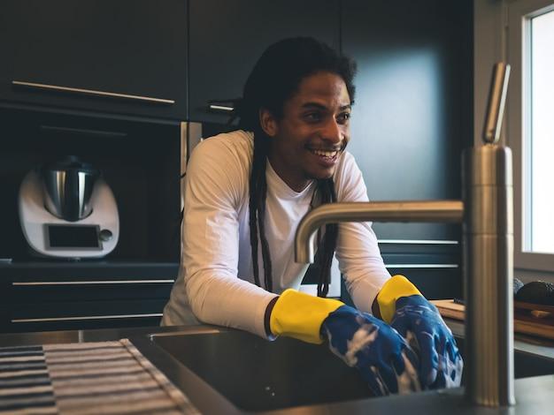 Joven negro con rastas recostado contra el fregadero sonriendo después de fregar
