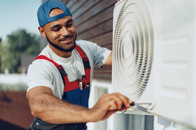 Joven negro reparador comprobando una unidad de aire acondicionado exterior
