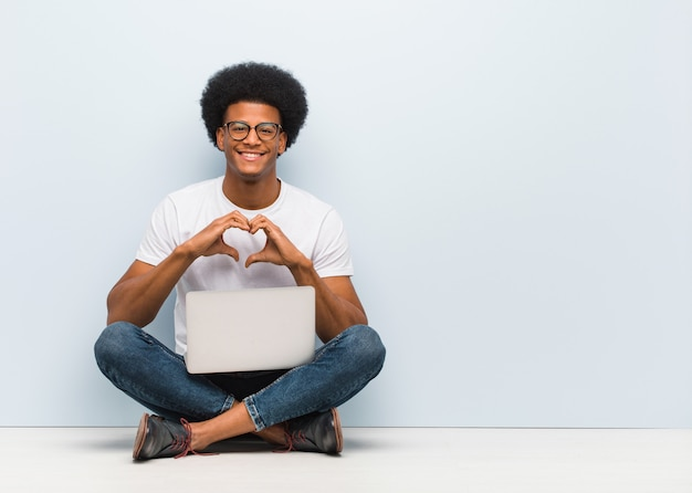 Joven negro sentado en el piso con un portátil haciendo una forma de corazón con las manos