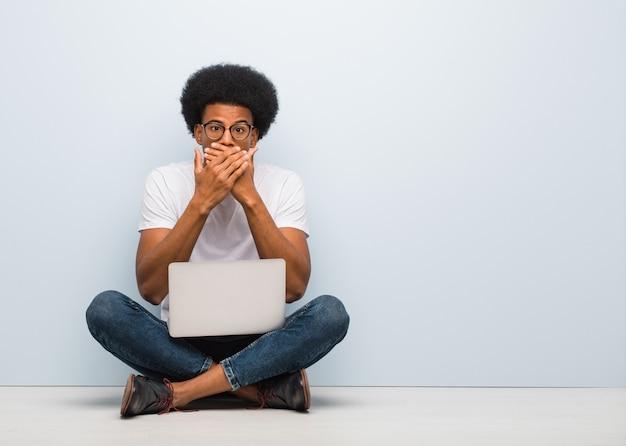 Joven negro sentado en el suelo con un portátil sorprendido y conmocionado
