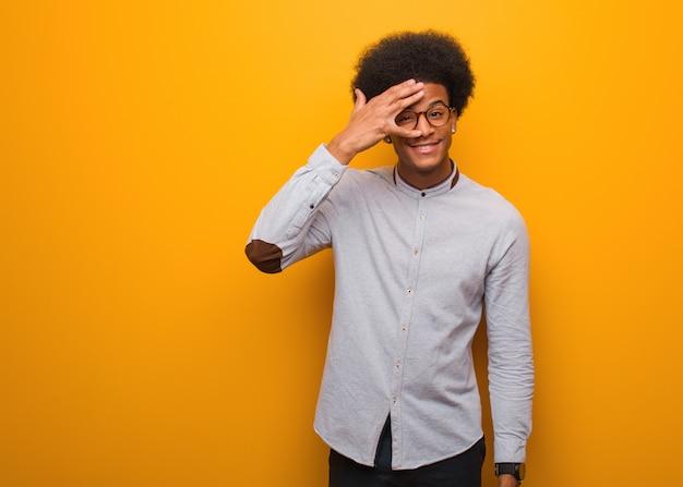 Joven negro sobre una pared naranja avergonzado y riendo al mismo tiempo