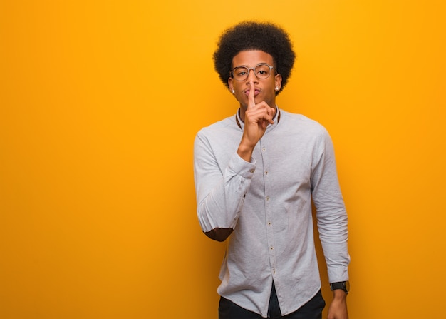 Joven negro sobre una pared naranja guardando un secreto o pidiendo silencio