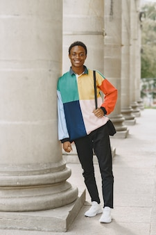 Joven negro sonriendo en la ciudad urbana. chico mixto con un suéter colorido.