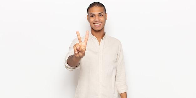 Joven negro sonriendo y mirando amistosamente, mostrando el número dos o el segundo con la mano hacia adelante, contando hacia atrás