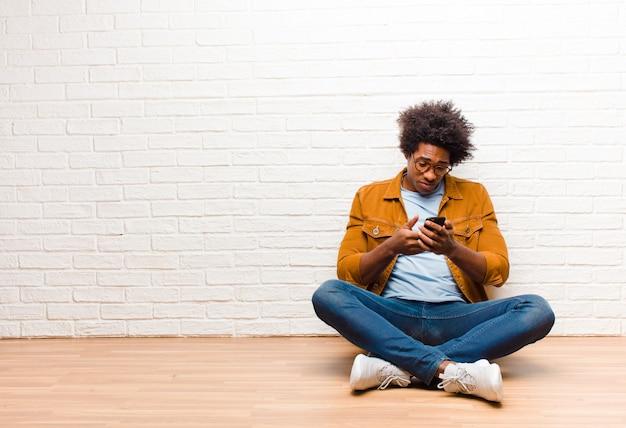 Joven negro con un teléfono inteligente sentados en el suelo