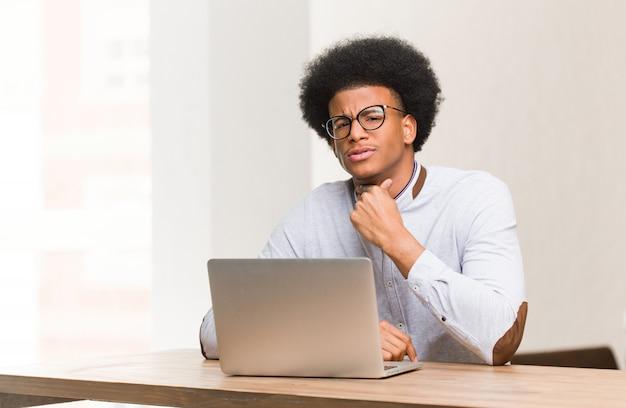 Joven negro usando su computadora portátil tos, enfermo debido a un virus o infección