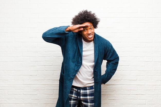 Joven negro vistiendo un pijama con una bata que parece desconcertada y asombrada, con la mano sobre la frente mirando a lo lejos, observando la pared de ladrillo