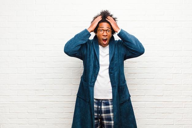 Joven negro vistiendo pijama con bata sintiéndose horrorizado y conmocionado, levantando las manos a la cabeza y entrando en pánico ante un error