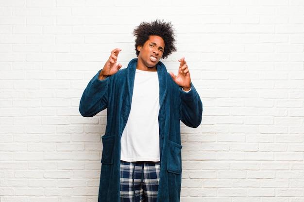 Joven negro vistiendo pijamas con bata cruzando los dedos con ansiedad y esperando buena suerte con una mirada preocupada contra el ladrillo