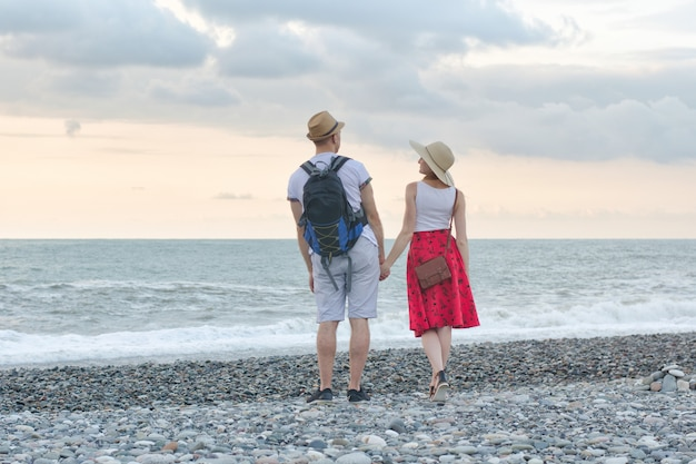 Joven y niña están de pie en la playa y cogidos de la mano