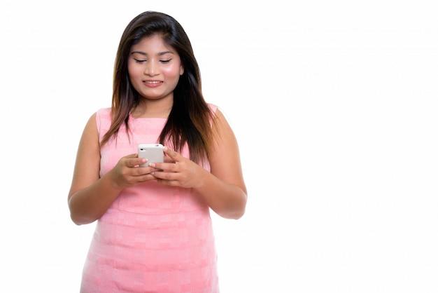 Joven niña persa feliz sonriendo mientras usa un teléfono móvil