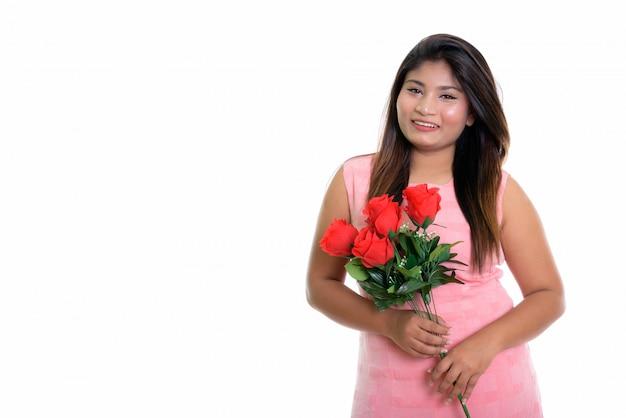 Joven niña persa feliz sonriendo y sosteniendo un ramo de rosas
