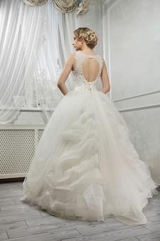 Joven novia hermosa, mujer en vestido de novia blanco largo en pentecostés
