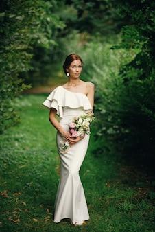 Joven novia hermosa con ramo de flores en un vestido blanco de pie solo al aire libre