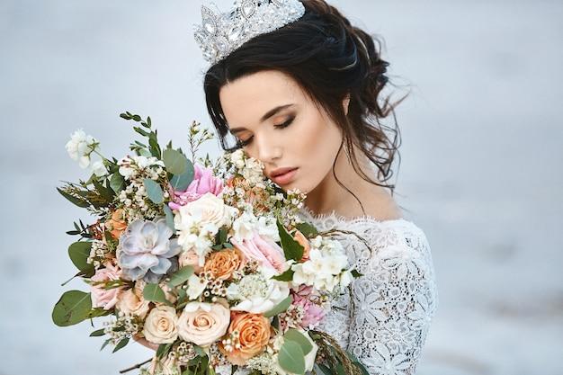 Joven novia con peinado de novia y diadema de lujo con un gran ramo de flores exóticas en sus manos