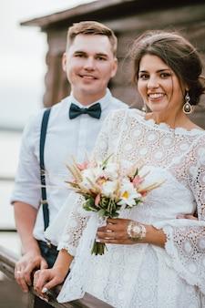 Joven novia sonriente con ramo de estilo boho con novio