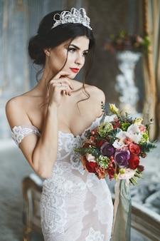 Joven novia en vestido de encaje posando con ramo de novia