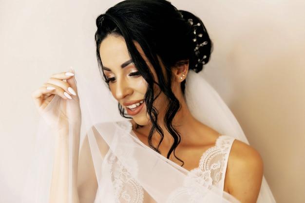 Joven novia en vestido de novia con ramo, foto de estudio