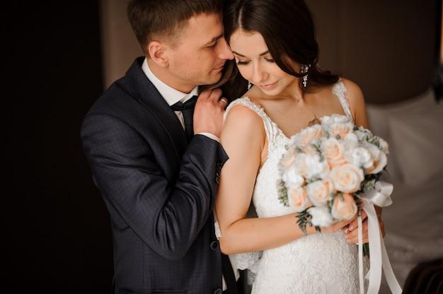 Joven novio abraza suavemente a su encantadora novia con un ramo
