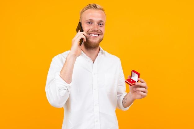 Joven novio con una camisa blanca hace una propuesta de matrimonio a la novia con un anillo en una caja y hablando por teléfono en amarillo