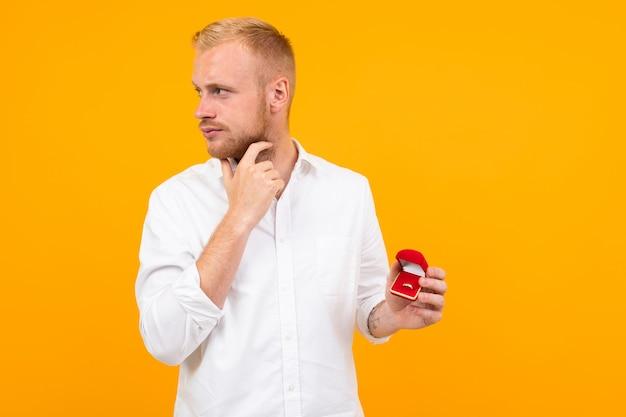 Joven novio con una camisa blanca hace una propuesta de matrimonio a la novia sosteniendo un anillo sobre un fondo amarillo