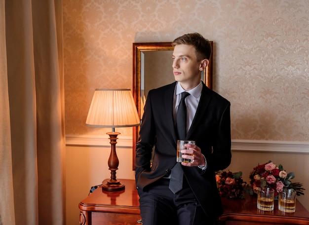Joven novio caucásico vestido con elegante esmoquin bebiendo alcohol en la habitación y sentado en la mesa junto a ramos de novia