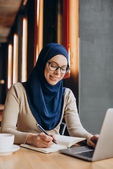 Joven nuslim que trabaja en línea en la computadora en un café
