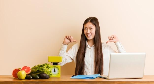 Joven nutricionista china que trabaja con su computadora portátil se siente orgullosa y segura de sí misma, ejemplo a seguir.