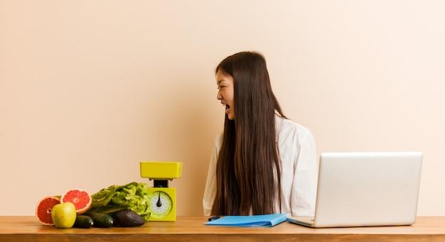 Joven nutricionista china trabajando con su laptop gritando hacia un espacio de copia