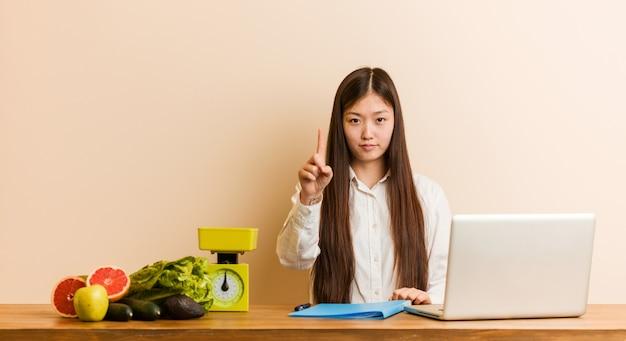 Joven nutricionista mujer china que trabaja con su computadora portátil que muestra el número uno con el dedo