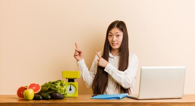 Joven nutricionista mujer china que trabaja con su portátil sorprendido señalando con los dedos índices