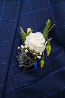 Un joven o novio en una camisa blanca, pajarita y chaleco a cuadros azul o chaqueta. hermoso boutonniere de rosas blancas y hojas verdes en un chaleco de bolsillo o solapa. tema de la boda