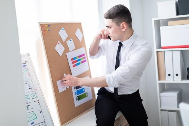 Un joven en la oficina de pie cerca de la junta con pegatinas y hablando por teléfono.