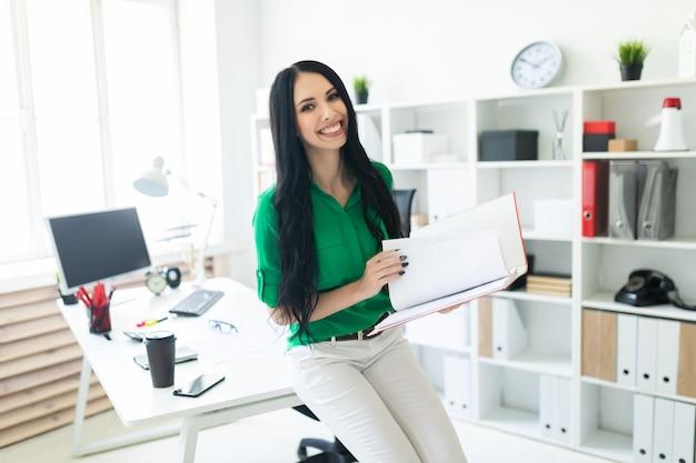 Una joven en la oficina se sentó en la mesa y sostenía una carpeta con documentos.