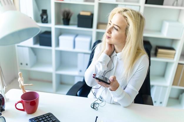 Una joven en la oficina se sienta en un escritorio con un teléfono en la mano y hablando a través de unos auriculares.
