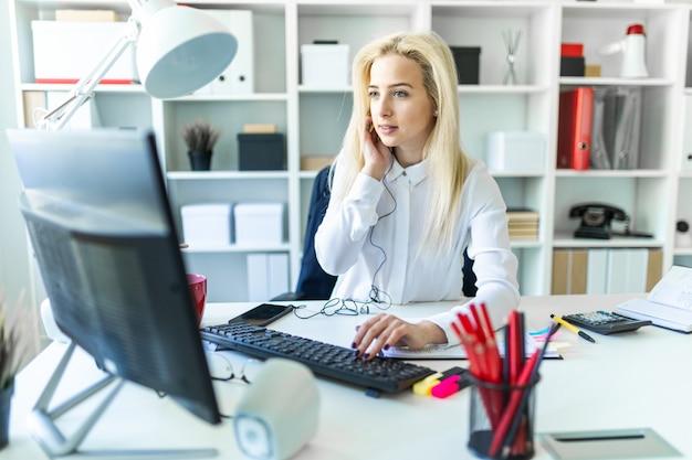 Una joven en la oficina se sienta en una mesa hablando por teléfono a través de unos auriculares y trabajando en la computadora