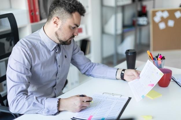Un joven en la oficina se sienta en una mesa, sostiene un marcador en la mano y trabaja con documentos.