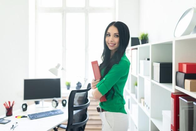 Una joven en la oficina sostiene una carpeta con documentos.