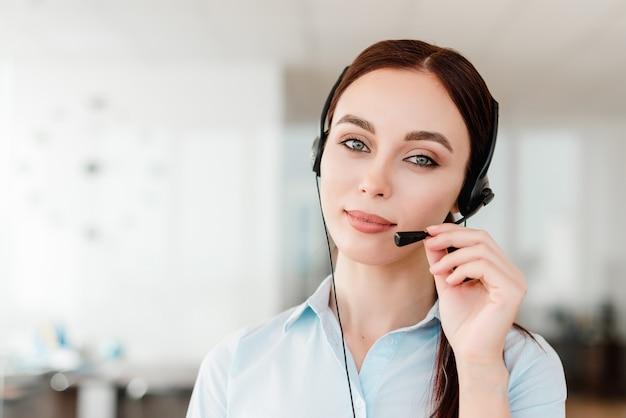 Joven oficinista con un auricular que responde en una llamada cente hablando con clientes