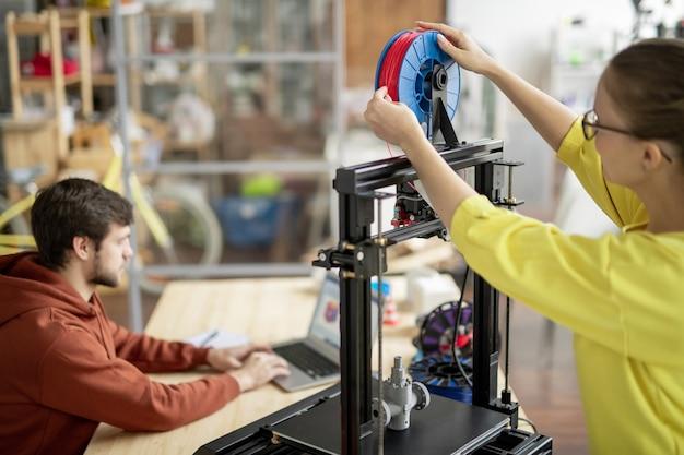 Joven oficinista cambiando el carrete con filamento rojo en la impresora 3d con redes de colegas