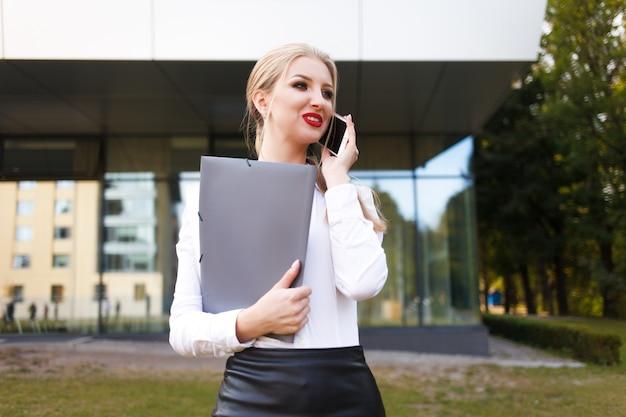 Joven oficinista hablando por teléfono con una carpeta en sus manos